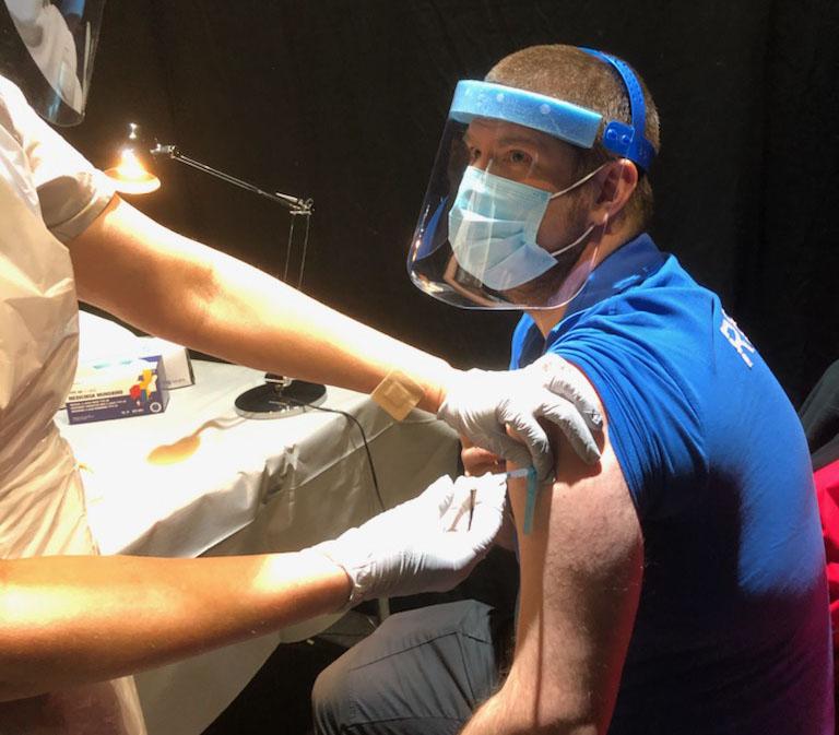 Man med visir får vaccinationsspruta.