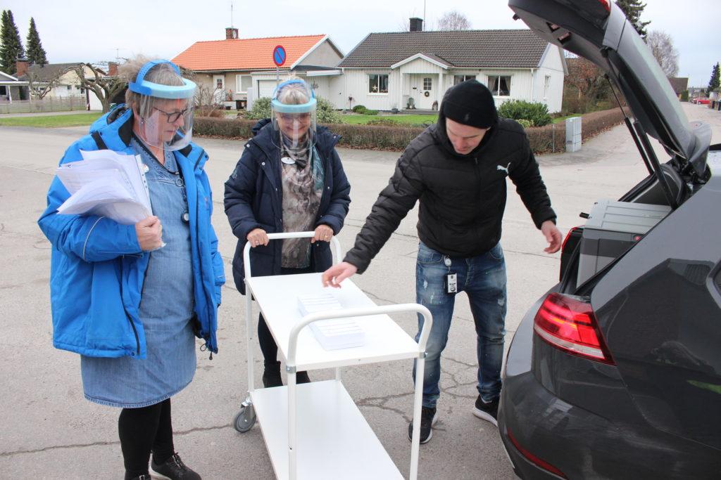 Tre personer lastar vaccin på en vagn.