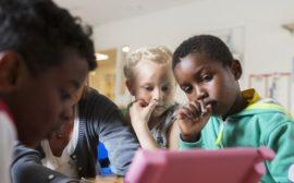 Bilden föreställer förskolebarn som sitter framför en läsplatta.