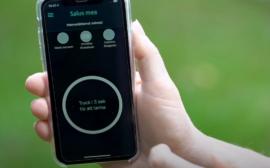 Hand håller i mobil som visar app med mobilt trygghetslarm.