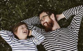 Bildens föreställer ett skrattande barn och en man.