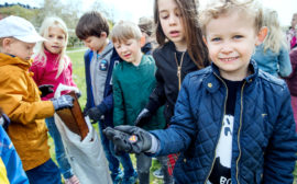 Fem barn varav ett visar upp skräp och en annan håller i en påse med skräp.