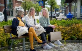 Tre kvinnor sitter på en bänk och pratar.