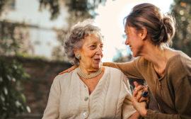 En kvinna håller armen om en äldre kvinna.