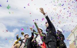 En grupp ungdomar dansar och firar att de har tagit studenten.