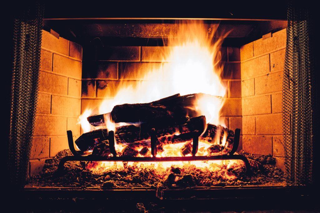 Bilden visar en öppen spis där ved brinner