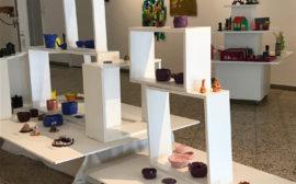Olika typer av konst på vita podier i en utställningshall