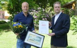 Två män varav den ena håller i blommor och en tavla, den andra ett diplom.