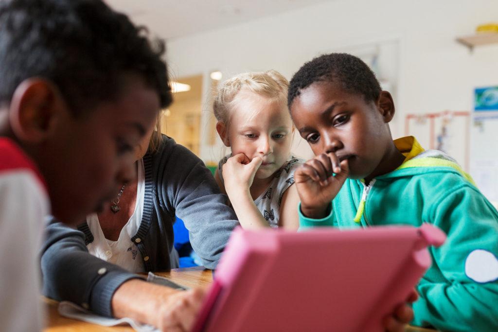 Bilden visar barn som sitter runt en läsplatta.