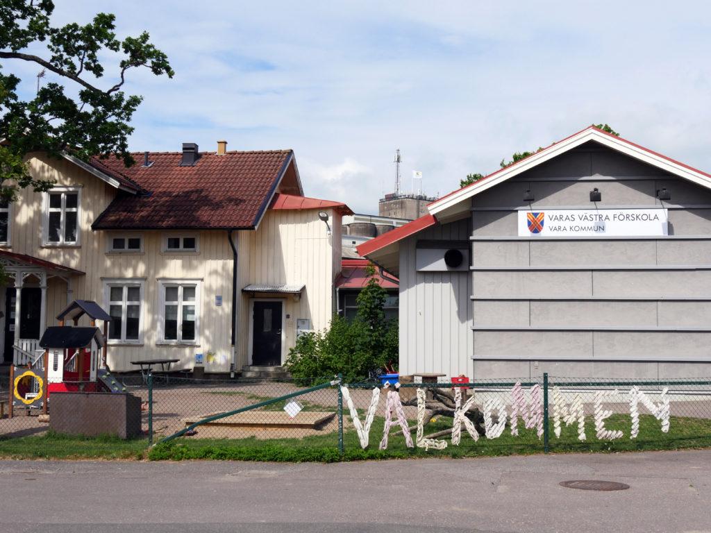 Bilden visar Varas västra förskola. Två byggnader och ett staket med texten välkommen.