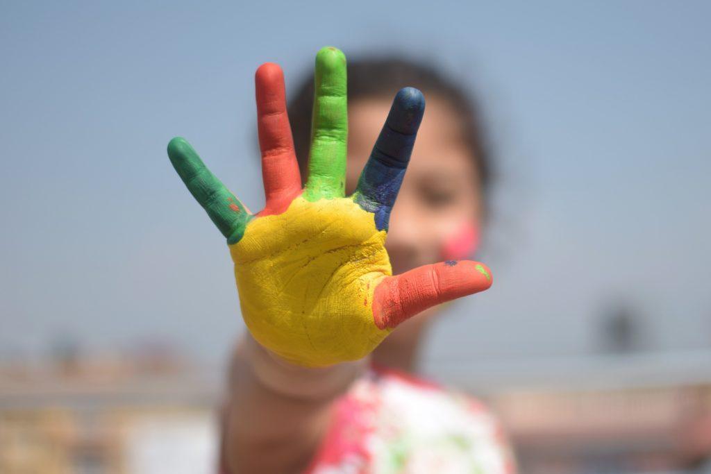 Bilden visar en färgglad barnhand.