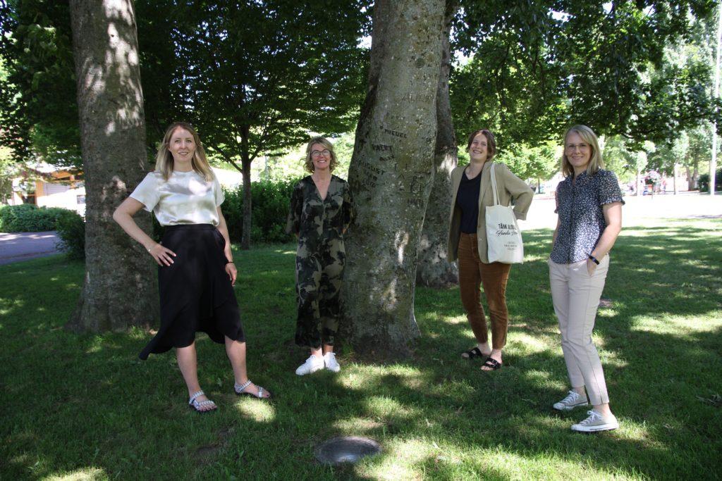 Fyra kvinnor på rad framför ett stort träd.