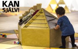 Ett litet barn utforskar en ljudmakapär. Text Kan själv!