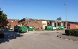 Skolbyggnad med containrar framför.