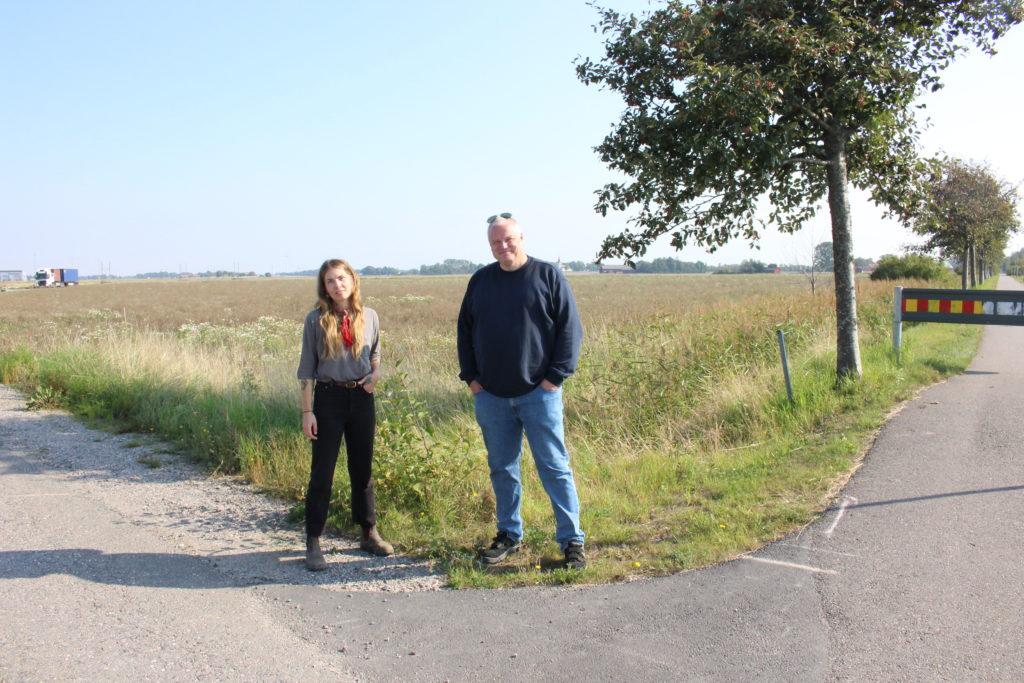 En kvinna och en man står i ett vägskäl framför ett fält.
