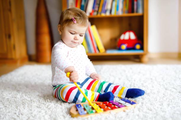 Bäbis sitter på matta och leker med en xylofon