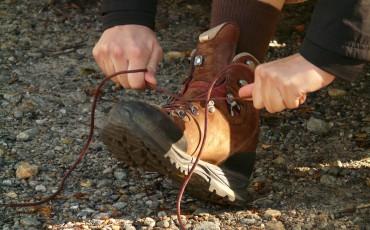 Någon som knyter en brun vandringskänga på grusunderlag